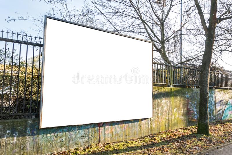 Cartelera en blanco en una cerca en paisaje urbano fotos de archivo