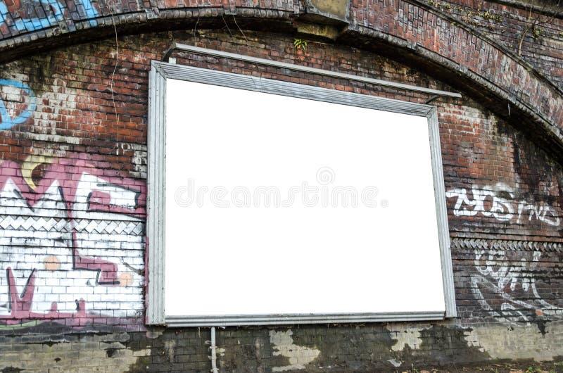Cartelera en blanco en una pared de ladrillo en el ambiente urbano imagen de archivo
