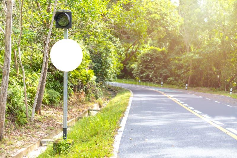 Cartelera o señal de tráfico en blanco blanca en el camino cerca de la madera verde imagenes de archivo