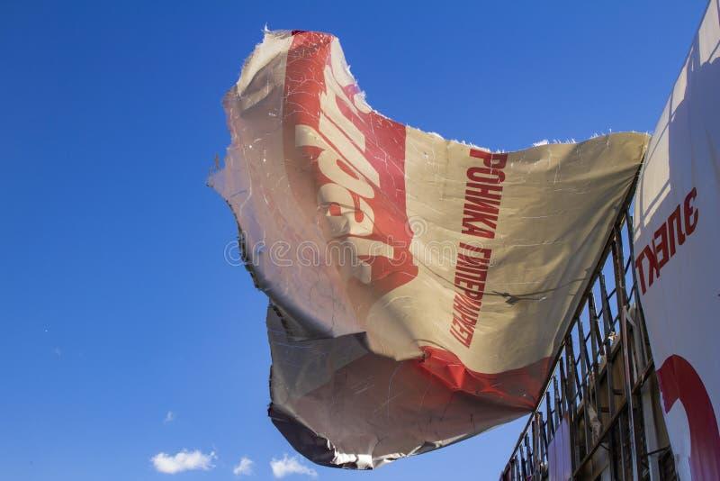 Cartelera rasgada que se convierte en el aire contra el cielo azul imagen de archivo libre de regalías