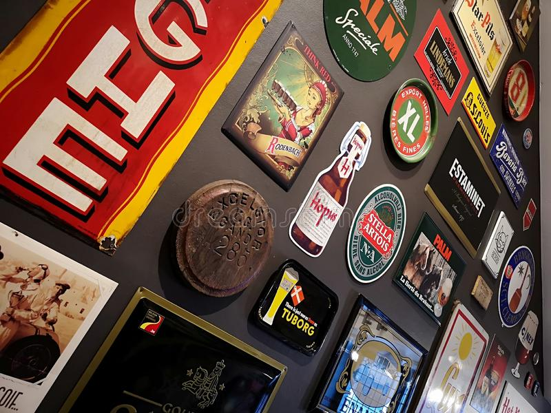 Carteles aadvertising de la cerveza en la pared imagenes de archivo