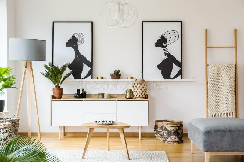Carteles africanos blancos y negros sobre el gabinete en la sala de estar internacional imagen de archivo