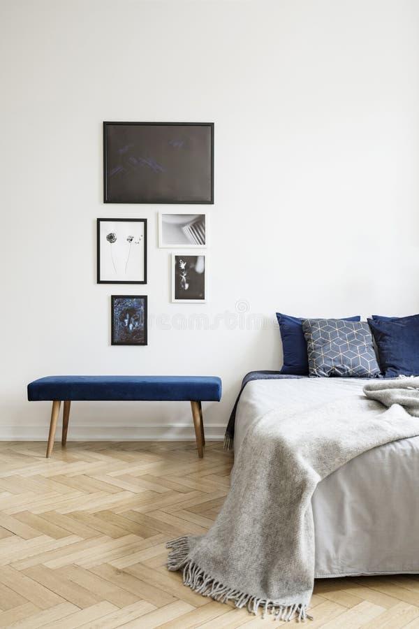 Carteles sobre banco azul al lado de la cama con la manta gris en el interior simple blanco del dormitorio Foto verdadera imagen de archivo