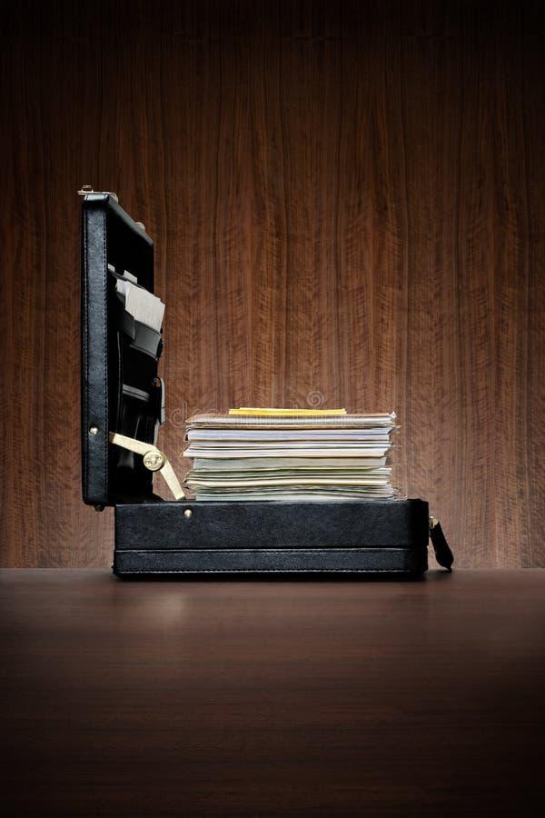 Cartella di cuoio nera con la pila del ambitiousl di archivi immagini stock