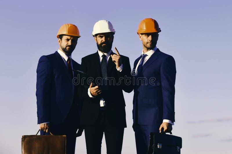 Cartella e cartelle della clip della tenuta degli architetti I capi con la barba ed i fronti interessati discutono il progetto immagini stock