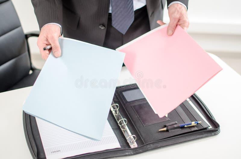 Cartelle della tenuta dell'uomo d'affari in sue mani immagini stock