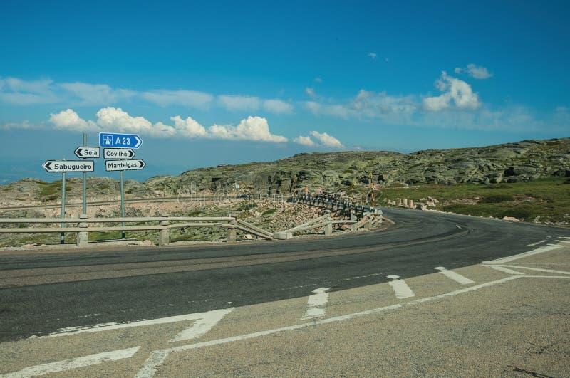 Cartelli con le direzioni della città sul paesaggio roccioso dell'incrocio di strada immagine stock