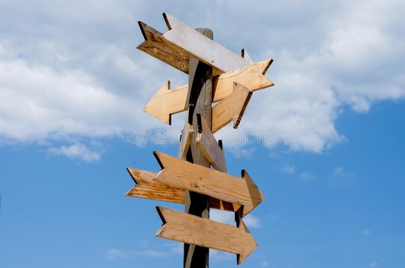 Cartelli di legno in bianco della freccia sul cielo blu di legno dei agains del palo fotografia stock