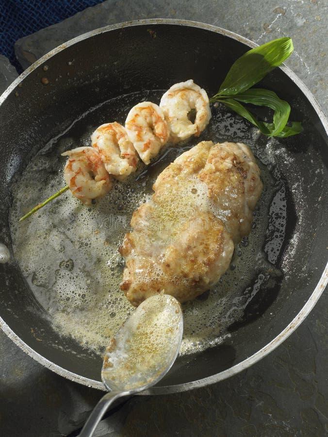 Carter-faire frire des ris de veau et un brochette de crevette images libres de droits