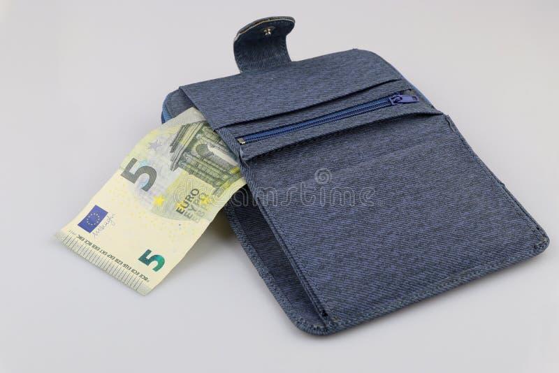 Cartera azul abierta con el billete de banco del euro 5 Aislado en el fondo blanco fotos de archivo