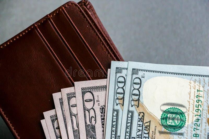 Cartera con cientos y cincuenta billetes de banco del dólar imagen de archivo libre de regalías