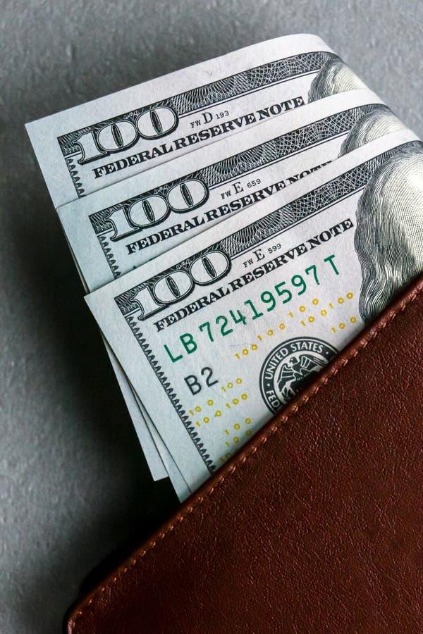 Cartera con cientos y cincuenta billetes de banco del dólar foto de archivo libre de regalías