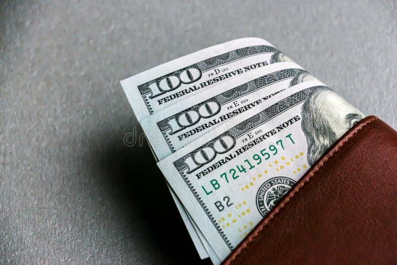 Cartera con cientos y cincuenta billetes de banco del dólar imagenes de archivo