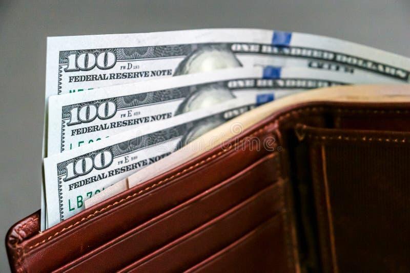 Cartera con cientos y cincuenta billetes de banco del dólar imagen de archivo