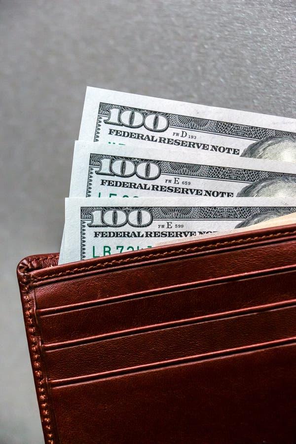 Cartera con cientos y cincuenta billetes de banco del dólar fotografía de archivo