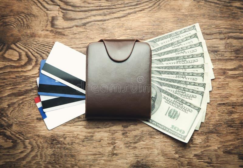 Cartera con las tarjetas y los dólares de crédito en un fondo de madera imagen de archivo libre de regalías