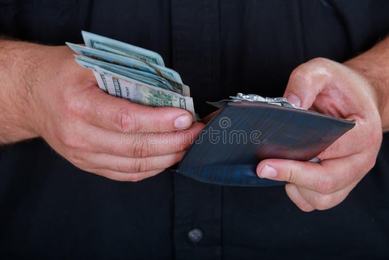 Cartera de cuero con el dinero en las manos masculinas en fondo oscuro fotos de archivo libres de regalías