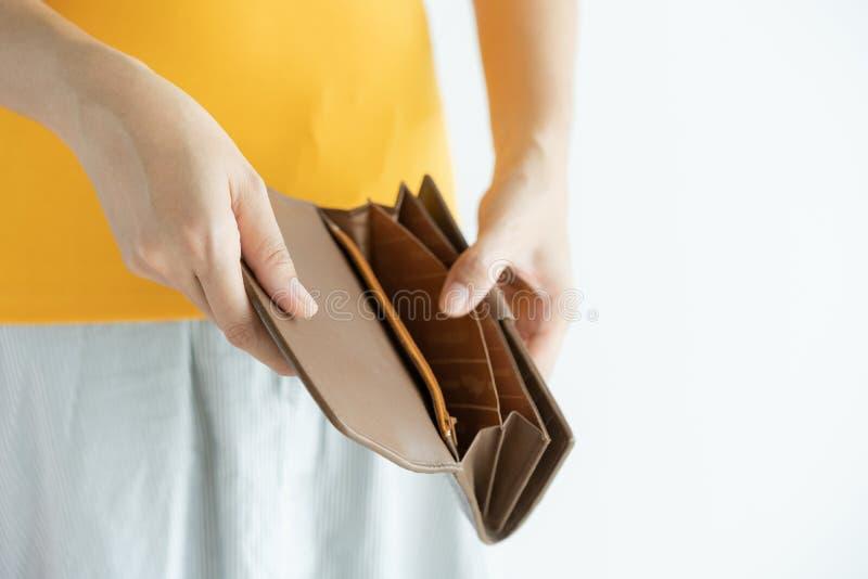 Cartera de cuero marrón vacía abierta de la mano de la mujer, dinero en bolsillo en el fondo blanco imagen de archivo libre de regalías