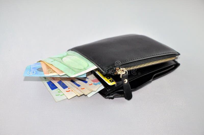 Cartera de cuero negra con el dinero euro imagenes de archivo
