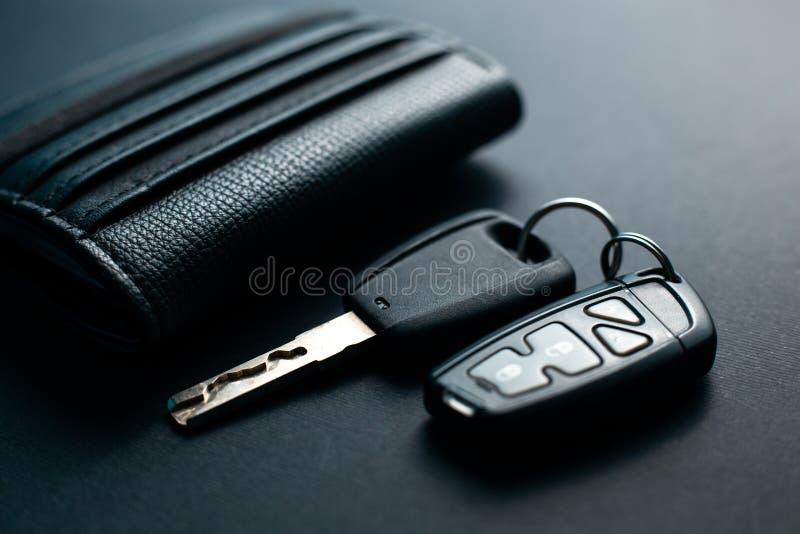 Cartera de cuero negra con llave del coche fotos de archivo