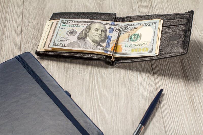 Cartera de cuero negra con los billetes de dólar, el cuaderno y la pluma fotografía de archivo