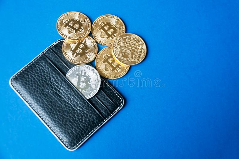 Cartera de cuero negra en un fondo azul con varios oro y monedas de plata de los bitcoins que caen de sus bolsillos imagen de archivo libre de regalías
