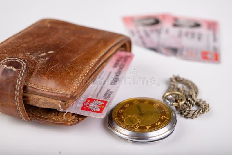 Cartera de cuero y un reloj viejo en una tabla blanca Documentos personales en la cubierta de cuero imagen de archivo libre de regalías
