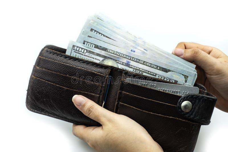 Cartera de la tenencia de la mano en los paquetes de 100 dólares americanos de billetes de banco foto de archivo