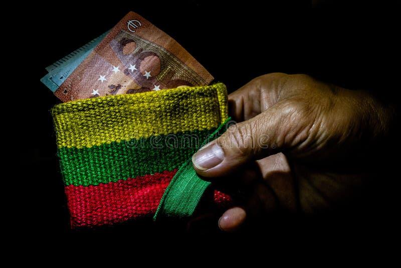 Cartera minimalista con colores cacerola-africanos, o colores de la bandera nacional de Lituania, a disposición de una persona imagenes de archivo
