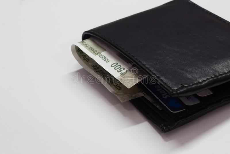 Cartera negra con el dinero aislado en el fondo blanco con el espacio para el texto imagenes de archivo