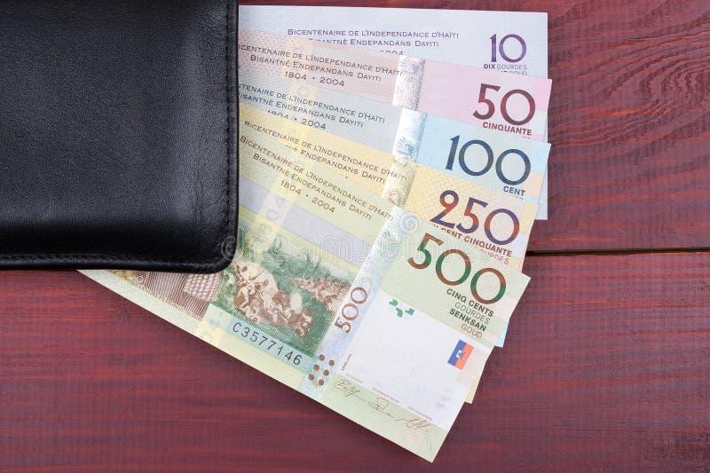 Cartera negra con el dinero haitiano imagen de archivo