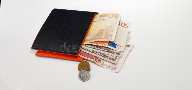 Cartera negra con las monedas euro de las rublos del dólar imagenes de archivo