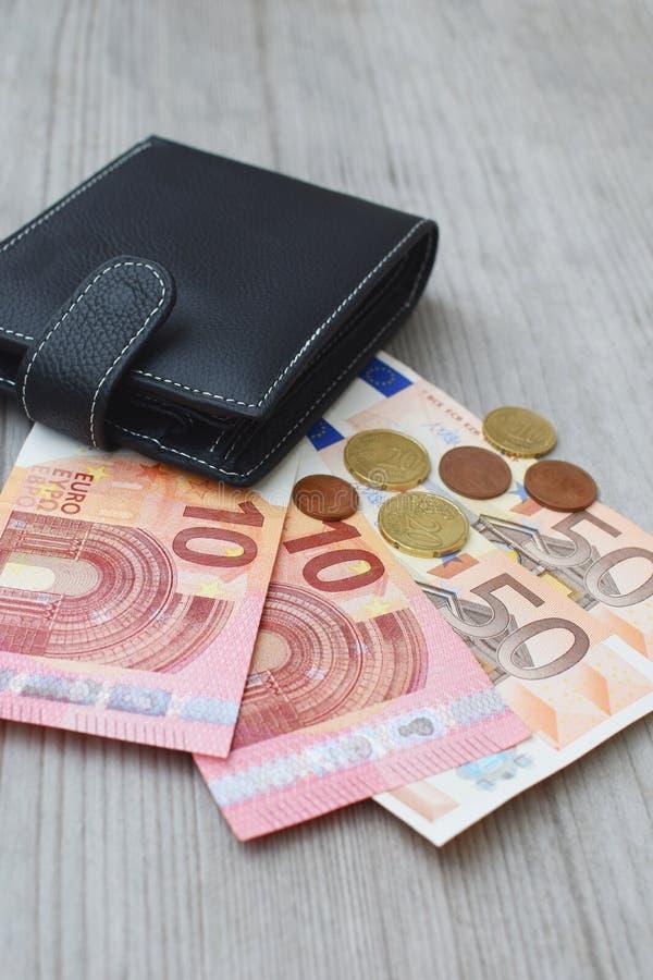 Cartera negra con los billetes de banco y las monedas euro de la moneda imagen de archivo