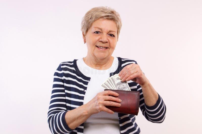Cartera que se sostiene femenina mayor feliz con las monedas dólar, concepto de seguridad financiera en edad avanzada fotos de archivo libres de regalías