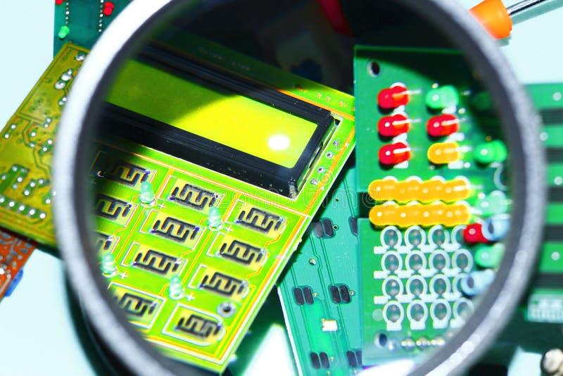 Cartes électroniques sur un fond bleu plus une loupe photographie stock