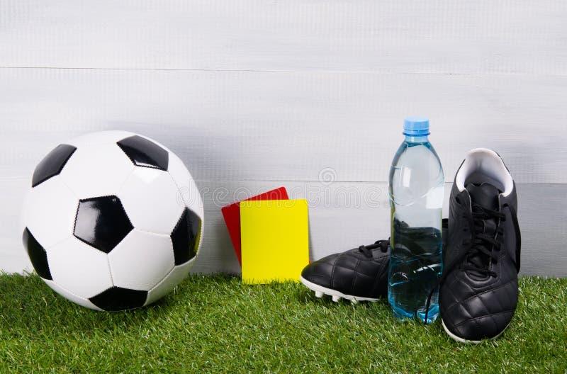 Cartes de bottes, de ballon de football, de bouteille d'eau et de pénalité pour le juge, support sur l'herbe, sur un fond gris po photographie stock libre de droits