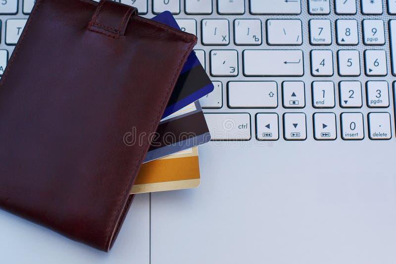 Cartes de crédit dans le portefeuille sur le clavier d'ordinateur portable photos libres de droits