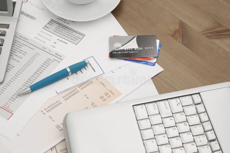 Cartes de crédit sur un ordinateur portable avec des déclarations de carte de crédit par tasse de ho photos libres de droits
