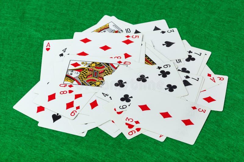 Cartes de jeu de casino sur la table verte images stock