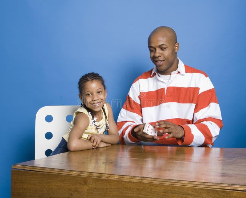 Cartes de jeu de petite fille avec le papa photos stock