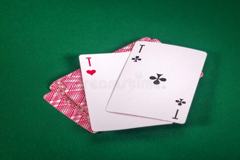 Cartes de jeu deux as sur la table verte image stock