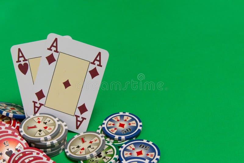 Cartes de pile et de jeu de jetons de poker - deux as sur la table verte image libre de droits