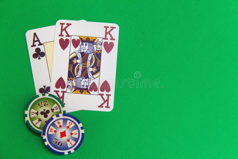 Cartes de pile et de jeu de jetons de poker sur la table verte photos stock