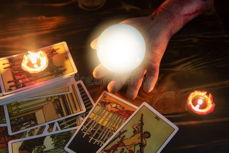Cartes de tarot et voyant de lecture de boule de cristal par lueur d'une bougie de main de zombi bien comme divination images stock