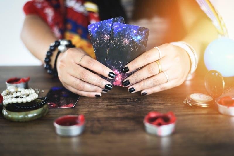 Cartes de tarot lisant des lectures de voyant de divination et le concept de voyance - mains de diseur de bonne aventure de boule image stock