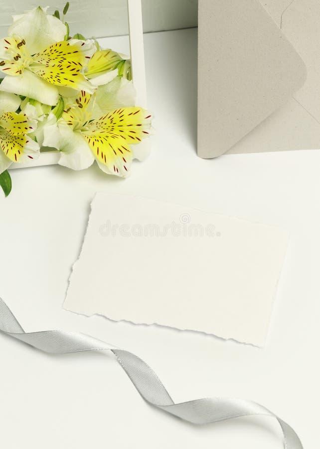Cartes de visite professionnelle de visite de maquette sur le fond blanc, les fleurs fraîches et le cadre photographie stock libre de droits