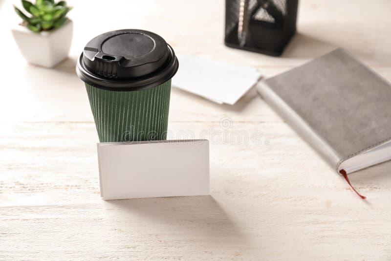 Cartes de visite professionnelle vierges de visite avec la tasse de café sur la table en bois photographie stock