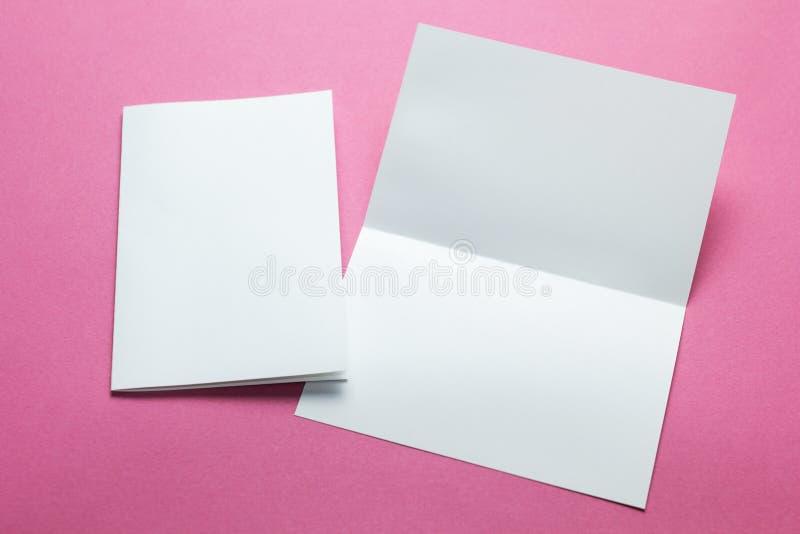 Cartes vides blanches d'isolement sur le fond rose pour remplacer votre conception, maquette photographie stock libre de droits