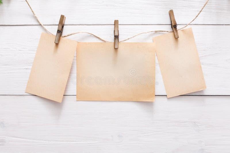 Cartes vierges sur la corde sur le fond clair de mur image stock