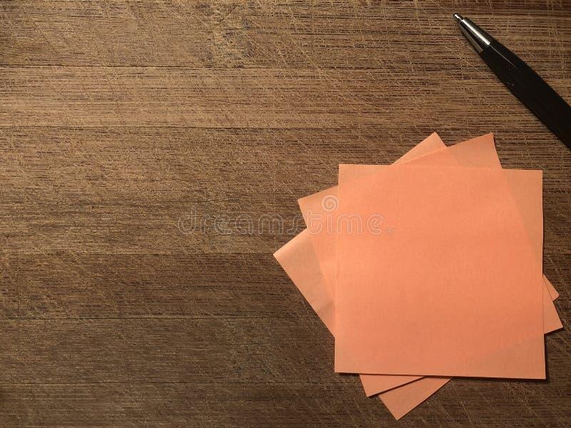 Cartolina con carta per appunti appiccicosa arancio e penna su fondo marrone di legno fotografie stock